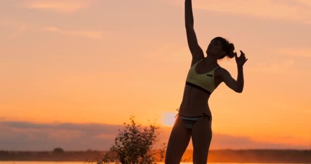 Střední plán volejbalového hráče při západu slunce při pomalém pohybu zpátky na kouli