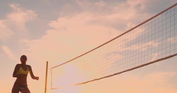 Mladíci ženského volejbalu procházejí a za slunného letního večera prohřejí míč přes síť. Na plážový volejbal při západu slunce