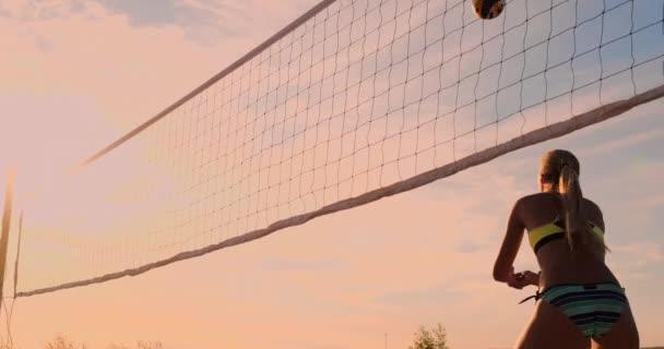 Skupina mladých dívek hraje plážový volejbal při západu slunce nebo sunrise.