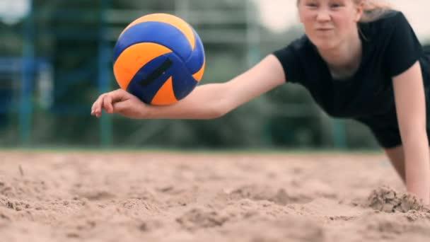 Női röplabda játékos ősszel eléri a labdát lassítva a strandon.