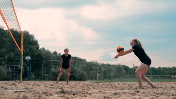 Ženy soutěží v turnaji profesionálních plážových volejbal. Obránce se pokouší zastavit záběr na 2 ženy mezinárodní profesionální plážový volejbal