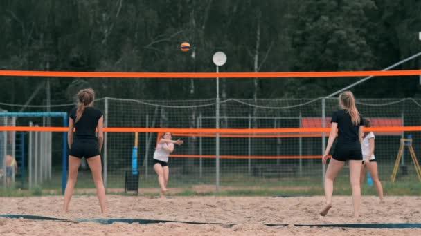 Mladá žena hrající volejbal na pláži v týmu, který provádí útok na míč. Dívka v pomalém pohybu zasáhne míč a provede útok sítí