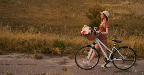 Pohled ze strany: usměvavá dívka v šatech s motorkou v létě na držadlu s květinami.