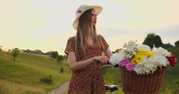 Young smiling blonde in hat and dress walking in dress with bike and flowers in basket.