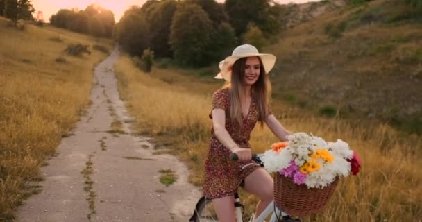 Happy girl with a bouquet of flowers riding a bike in a hat and a summer short dress.
