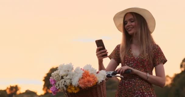 Beautiful blonde in a hat with a bike looking at the mobile phone screen and a basket on the handlebar with flowers.