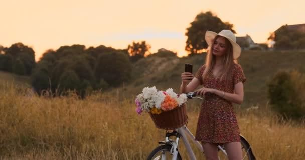 Gyönyörű szőke kalapot a kerékpáros nézi a mobiltelefon képernyőjén, és egy kosár a kormányon a virágok.