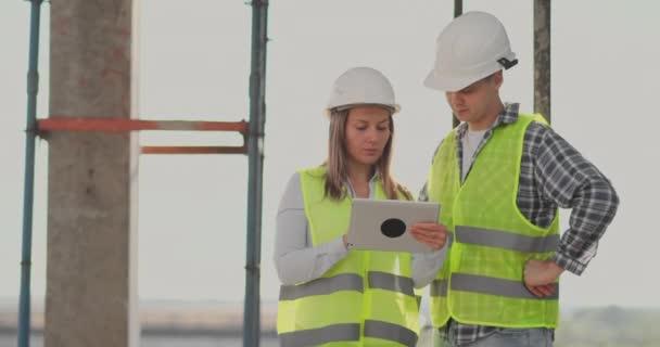 Staveniště tým nebo architekt a stavitel nebo pracovník s přilepovy diskutují o plánu stavebních prací či plánech na popraviště.