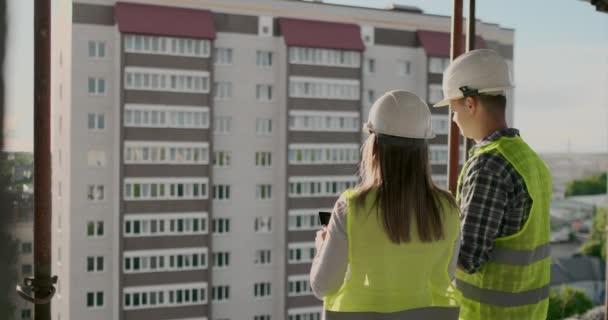 Stavební dělníci pracující na staveništi, stavitelé se dívají na modři, dozadu, na kopírovací místo. Koncepce stavby, rozvoje, týmové práce a lidí