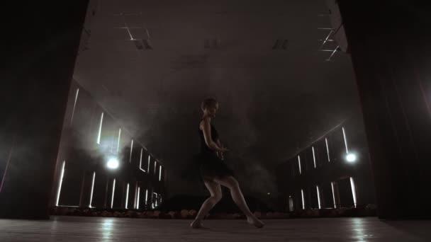 Kecses balerina fehér ruhában tánc elemei a klasszikus vagy modern balett a sötétben.