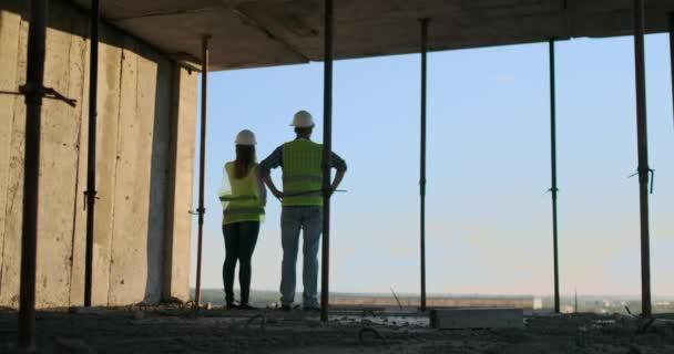 Pohled na kavkazského tvůrce v bílé helmě a na zelené vestě s výhledem na nedokončený stavební podklad