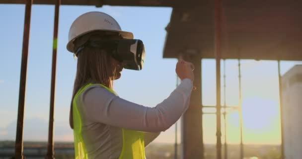 Znalecký inženýr v VR brýle a přilba kontroluje postup mrakodrapu, který při západu slunce vizualizuje stavební plán.