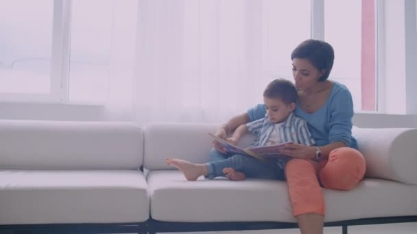 Happy mother and little son reading a book in the morning together in the living room at home. family activity concept