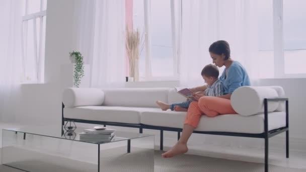 Mladá matka s dítětem, která čte knížku v jasně bílém interiéru domu v obývacím pokoji na gauči.