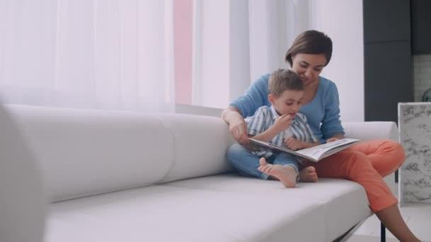 Milující matka učí svého syna, aby četl knihu hospodářství mluvení na gauči doma.