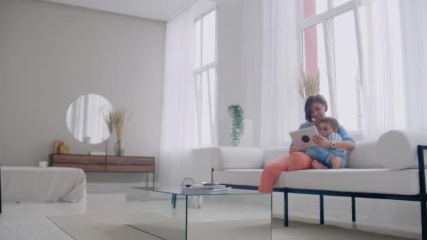 Šťastná rodinná máma a syn, kteří používají digitální tablety na pohovce, usmívající se rodič s dětsynem, který drží PC počítač a dívá se na obrazovku on-line nakupování dělá video.
