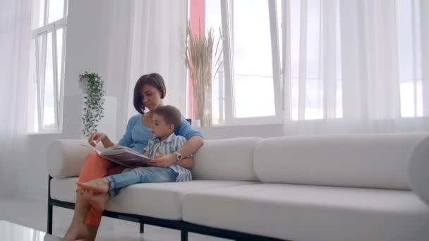 eine junge Mutter mit einem Kind, das ein Buch liest, sitzt in einem hellen weißen Inneren des Hauses im Wohnzimmer auf der Couch.