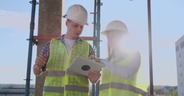 Construction site Team or architect and builder or worker with helmets discuss on a scaffold construction plan or blueprint or checklist.