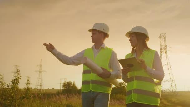 Spolupracující inženýři s tabletmi na solární továrně. Dospělí muži a ženy v tvrdých kloboucích, kteří v exteriéru stojí na transformátorové plošině. Doprava čisté energie