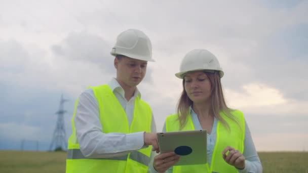 Power lines, man and woman engineers with a tablet in their hands check the progress of the installation of new towers and analyze the network.