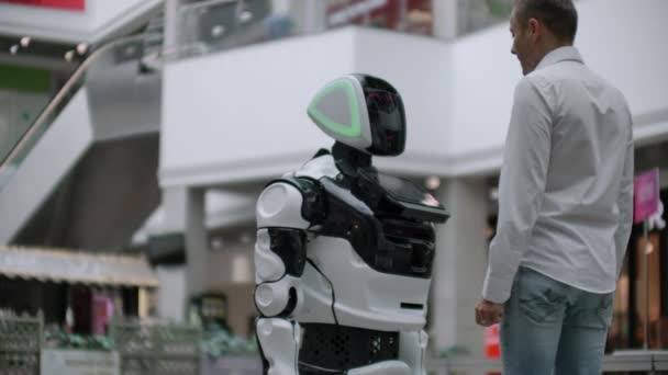 A man in a shirt communicates with a white robot asking questions and pressing the screen with his fingers.