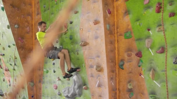 Climber moves on the mountain in a room with a rope on the insurance and a bag for chalk overcoming the height rises to the top in slow motion
