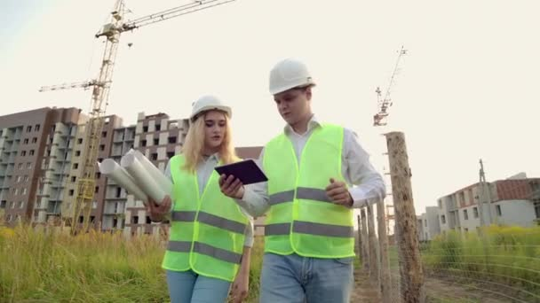 A man and a woman in protective clothing and helmets go to the construction site to discuss and look around click on the tablet screen on the background of working cranes