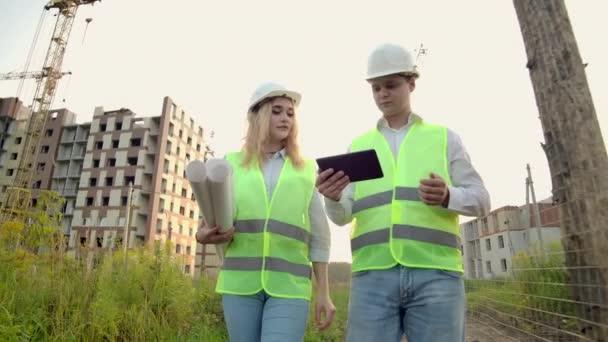 Dva průmysloví inženýrovi nosí bezpečnostní přilbu a drží v práci tabletové inženýrství a hovoří s prohlídkou výkresů. Na budovu venku. Inženýrské nástroje