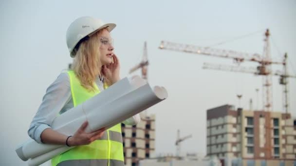Mluvící žena v helmě na telefonu na pozadí výstavby s jeřáby, který drží v ruce kresby. Ženský inženýr na staveništi.