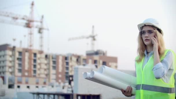 Bauarbeiterin telefoniert mit dem Bauunternehmer mit Zeichnungen in den Händen über den Hintergrund von im Bau befindlichen Gebäuden und Kränen.