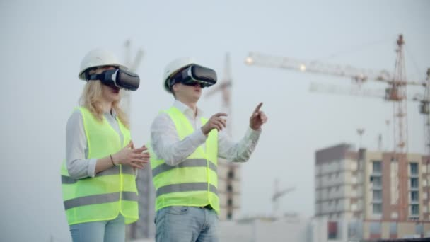 Two people in virtual reality glasses on the background of buildings under construction with cranes imitate the work of the interface for the control and management of construction