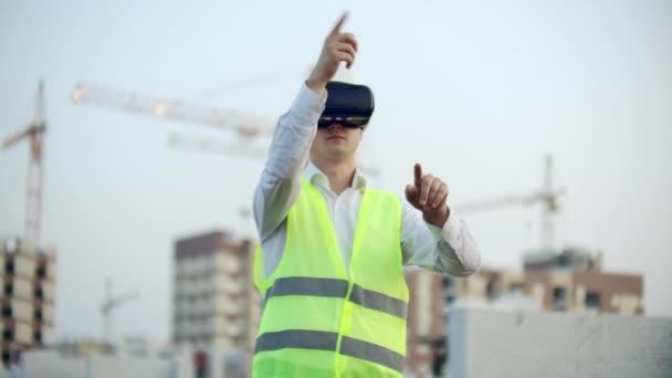 Porträt eines männlichen Inspektors, der mit einer Virtual-Reality-Brille die Arbeit von Bauarbeitern analysiert. ein Mann mit Helm und Schutzweste steht in vr Brille und bewegt seine Hände