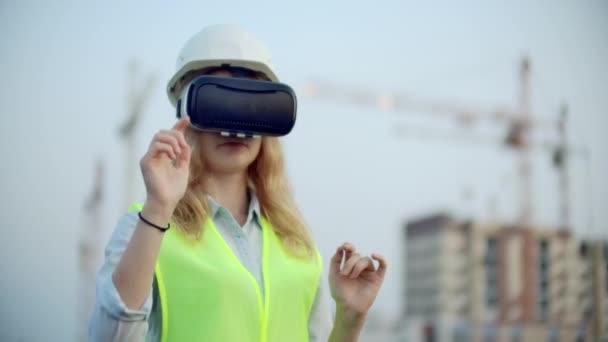 Designerin auf einer Baustelle in Harthut und Weste in der Brille der virtuellen Realität, um Ihre Hände zu bewegen, die das Interface auf dem Hintergrund der Kräne bei Sonnenuntergang imitieren