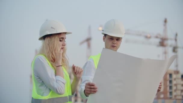 Dva stavitelé s kresbami na pozadí budov ve výstavbě v helmách a Vesti, Žena mluvící telefonicky s odběratelem