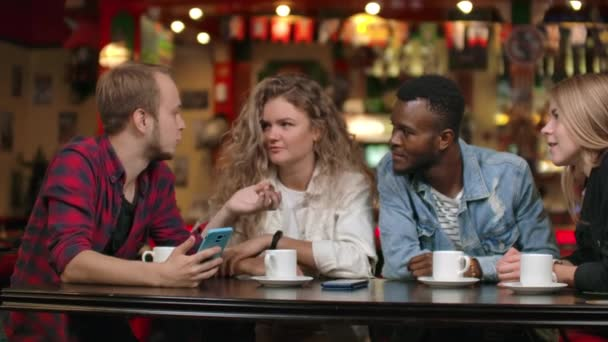 Cheerful company of friends at a bar drinking coffee laughing and discussing while looking at the smartphone screen