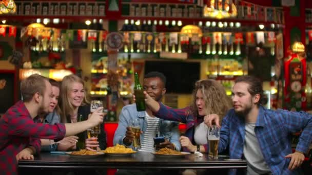 In a multi-ethnic company of friends, a girl offers a toast and friends banging glasses and bottles of beer while sitting in a bar. A fun evening in the company of friends