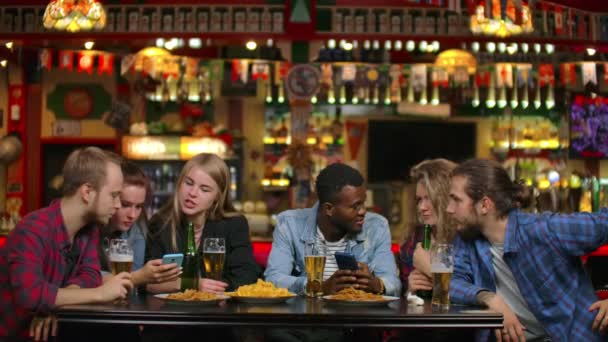 A man shows his friends a photograph on the phone and everyone laughs while paired and drinking beer