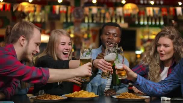 Close-up plan a company of friends makes a toast and everybody knocks, check their glasses with beer, drink, and laugh. Students meeting in a bar, restaurant