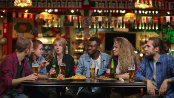 A multi-ethnic group of young men and women drink beer at a bar and eat chips and cheerfully debate about the university. Laughing at a joke