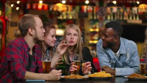 A large cheerful company of young people in the bar chatting, discussing the semester, the latest rumors, laughing and drinking beer. Multi-ethnic company