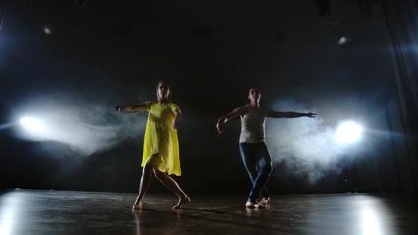 Zvětšit kameru. Moderní romantická choreografie. Láska je na jevišti. Muž a žena tančí spolu legrační tanec v džínách a žluté šaty na jevišti v dýmu. Hudební