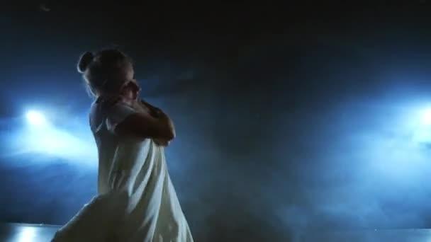 Eine Frau im weißen Kleid tanzt auf der Bühne die dramatischen Tänze des modernen Balletts. Eine Balletttänzerin bewegt Plastik und führt moderne Choreographien in Rauch auf
