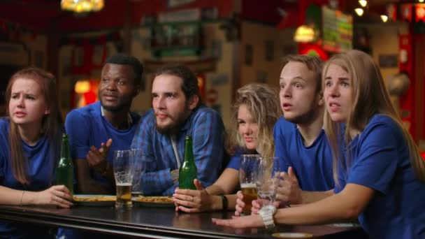 Emotional fans in blue t-shirts at the beer bar. Multi-ethnic group of African-American people are upset and sad because of the failure of their team.