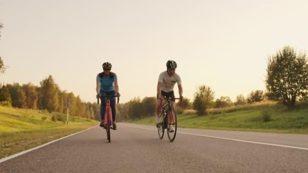 Steadicam-Aufnahme von Mountainbike-Paar, das bei Sonnenuntergang auf Radweg unterwegs ist