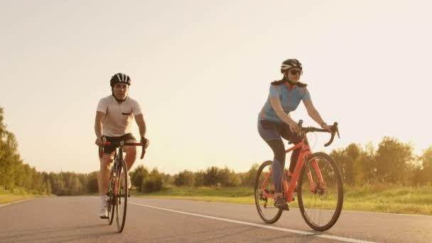 Muž a žena jezdí sportovní kola na dálnici při západu slunce v převodovce a ochranné přilby v pomalém pohybu 120 FPS