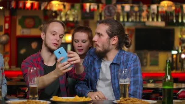 In der Bar oder im Restaurant macht der hispanische Mann ein Selfie von sich und ihren besten Freundinnen. Schöne junge Leute in stilvollem Lokal