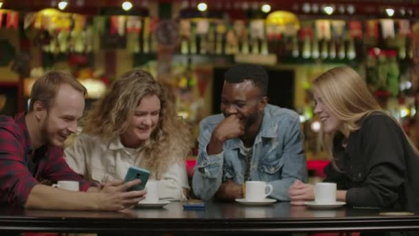 Happy multi-ethnic group of friends talking using smartphones at. Happy multi ethnic group of friends talking using smartphones in cafe, diverse young people.