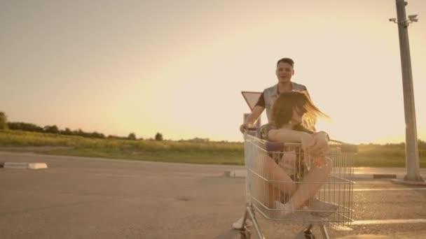 Boční pohled na mladou ženu a muže, který se baví venku na nákupních vozíky. Multietnické mladé lidi závodí na nákupních vozících. Na parkovací zóně s jejich