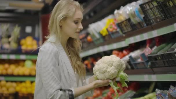 Krásná mladá bruneta dívka v její 20s vybírala napa zelí a květák a jejich uvedení do nákupního košíku na ovoce a zeleniny uličky, v obchodě.
