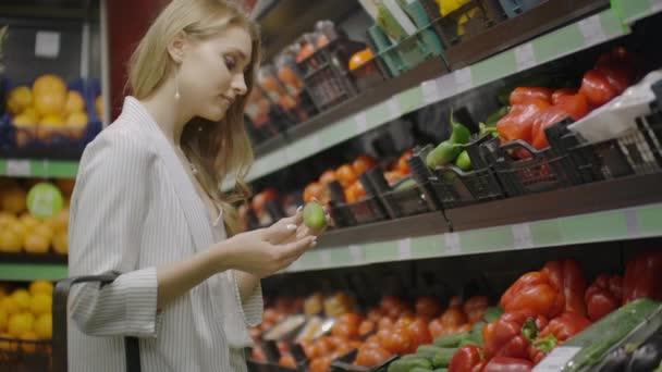 Egy nő kiválasztásánál figyelembe uborka, zöldség egy szupermarketben. Vásárlás kiválasztás vásárol gyümölcsöt, zöldség. Fiatal lány, nő kiválasztásában és vásárol paradicsomot és zöldséget. egészségvásárlás lány